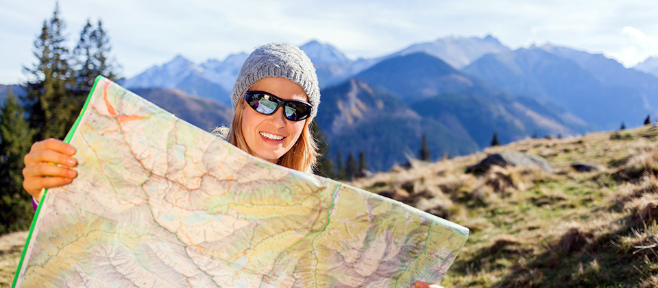 Woman is studying a route map in the mountains of South Tyrol
