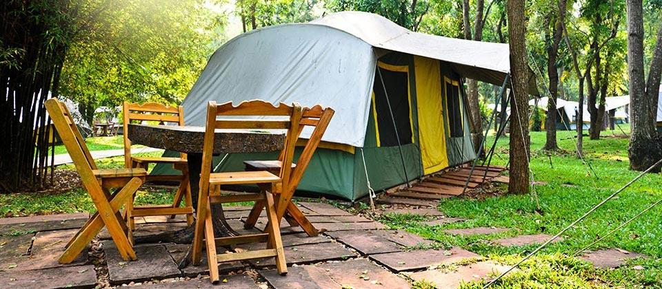 Tenda eretta nel verde con mobili da giardino