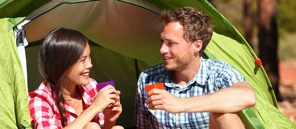 Smiling couple relaxing and drinking in front of a green tend in a campsite in South Tyrol