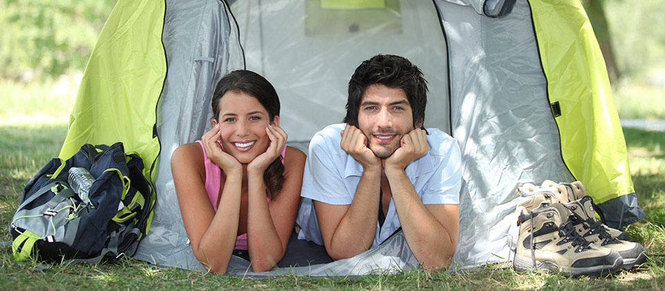 Smiling couple is looking out of their tend while relaxing in a campsite