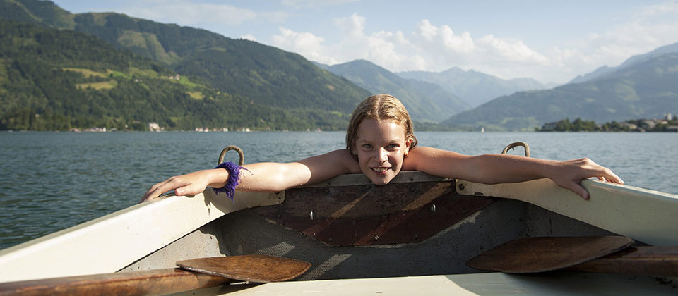 In the middle of the Lake of Caldaro a girl is trying to enter her boat after swimming