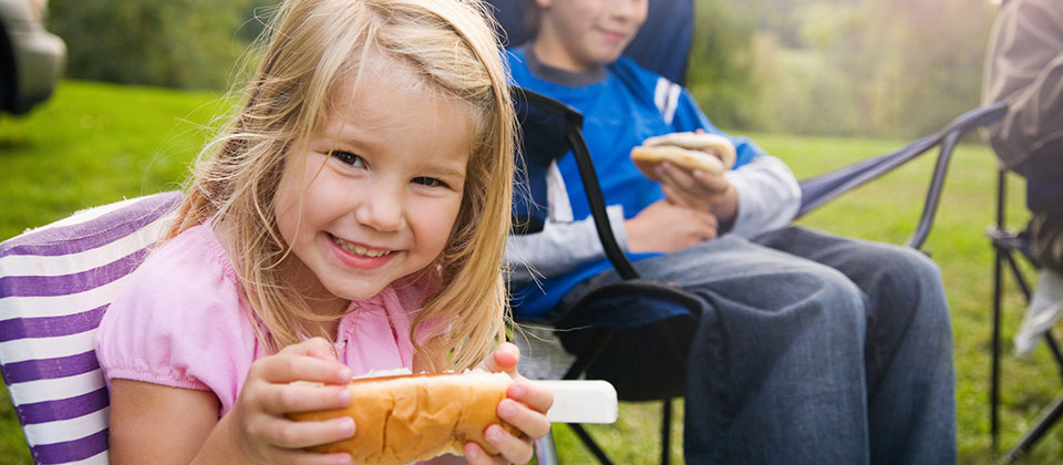 Smiling blond girl with a sandwich for snack