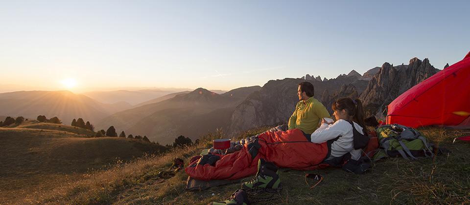 Ein Paar in ihren Schlafsäcken erfreut sich am Sonnenaufgang in den Dolomiten