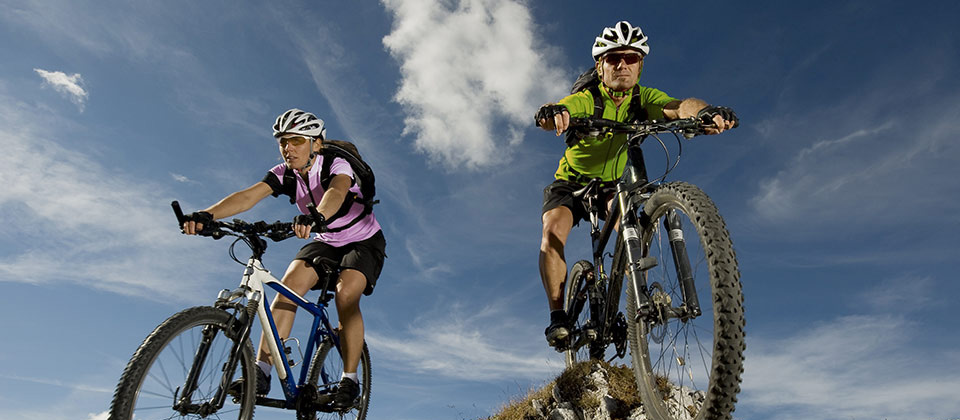 Sporty couple with mountain bikes in front of a partially clouded sky
