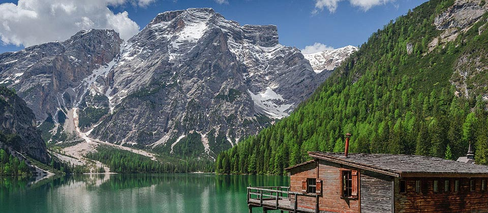 Small wooden house at the lake of Braies with snowy mountains in the background
