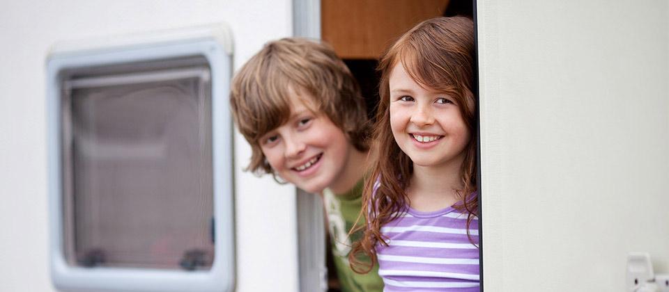 Zwei lachende und neugierige Kinder schauen aus ihrem Wohnwagen