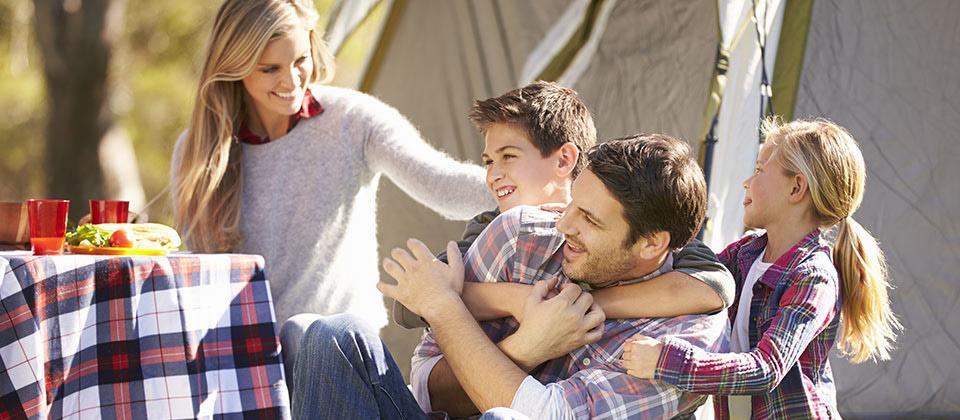 Eine fröhliche Familie in einem Camping in Südtirol beim Umarmen und Spielen