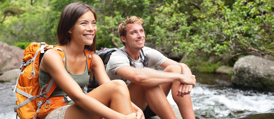 Ein Paar beim Ausruhen, sitzend auf den Steinen an einem Fluss in den italienischen Alpen