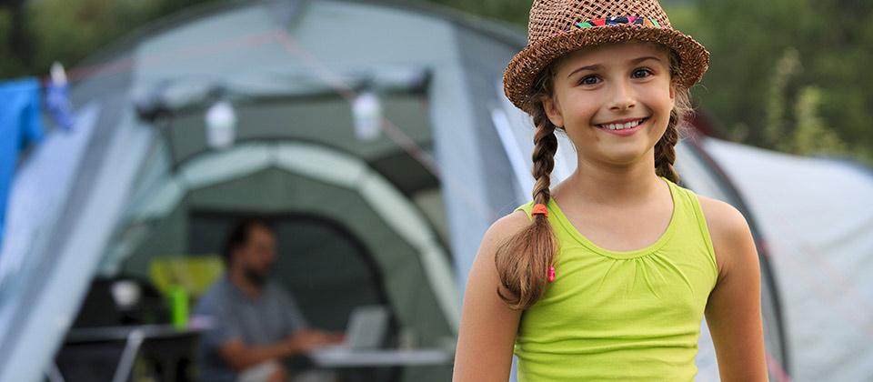 Ein fröhlich lächelndes Mädchen mit Strohhut vor ihrem Zelt im Vinschgau