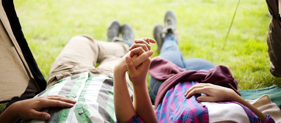 Ein händchenhaltendes Paar beim Entspannen im eigenen Zelt
