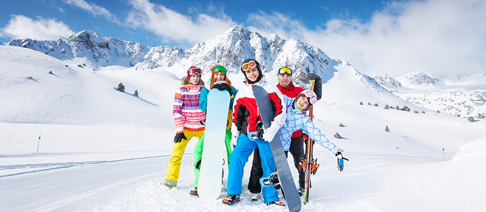 A family in South Tyrol after snowboarding in winter, surrounded by snowy peaks