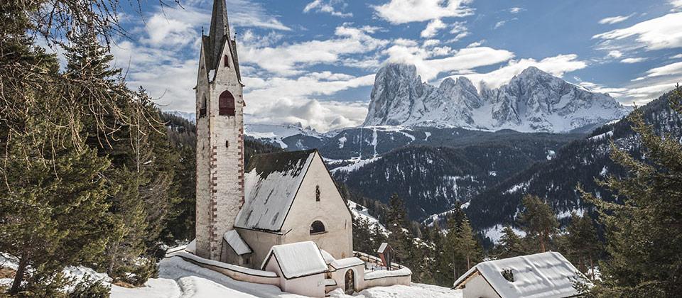 Die Kirche von St. Jacob gehüllt in Schnee mit den Langkofel Bergen als Hintergrund
