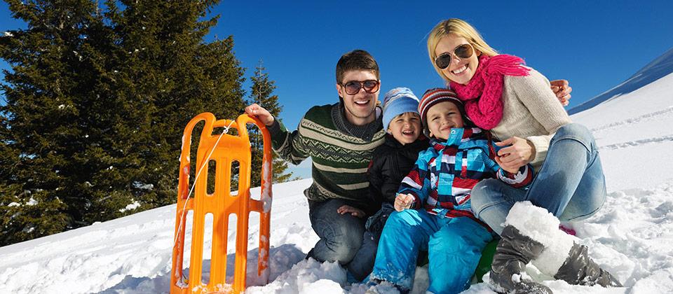 Fröhliche Familie sitzt nach einer Rodelfahrt zusammen im Schnee