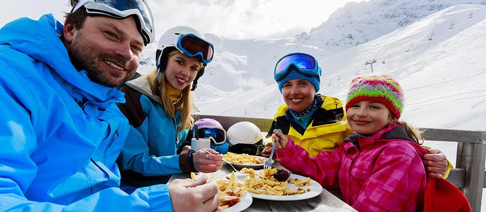 Familie mit 2 Kindern nach dem Skifahren beim Mittagessen: Kaiserschmarrn und Pommes