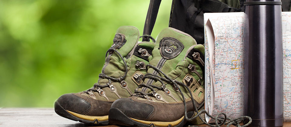 Details of a pair of walking boots, a map, a backpack and a drinking bottle