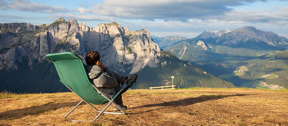 A man in a chair enjoying the view of the Dolomites from high up in the mountains