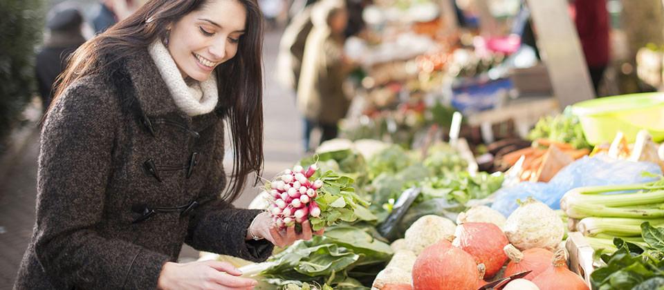 Donna curiosa tra gli ortaggi e le spezie al mercato delle erbe a Bolzano