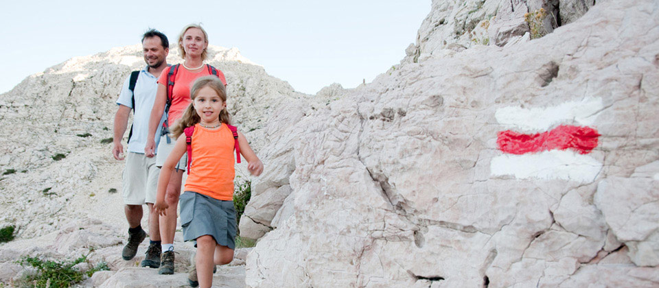 Trekking family finding their way in the trails of Plan de Corones thanks to marked stones