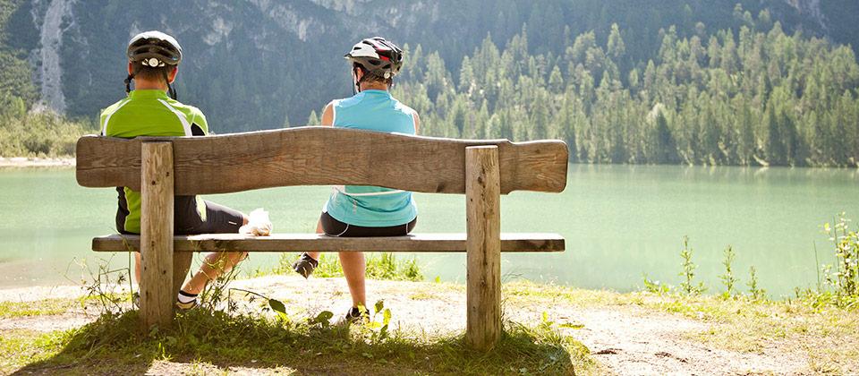 Ciclisti si risposano su una panchina di legno di fronte al lago di Braies