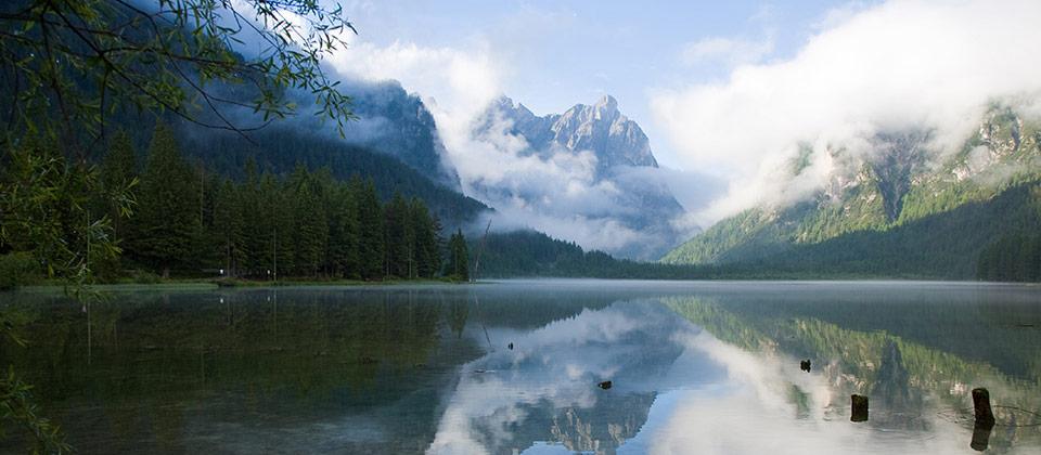 Der See von Toblach mit von Wolken umhüllten Gebirgsspitzen