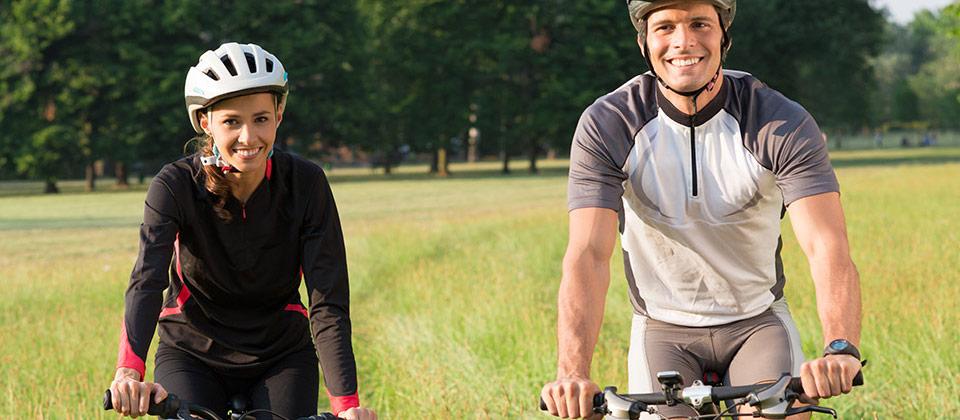 Ein Paar auf einer Mountainbike Strecke mitten in einer Wiese in Südtirol