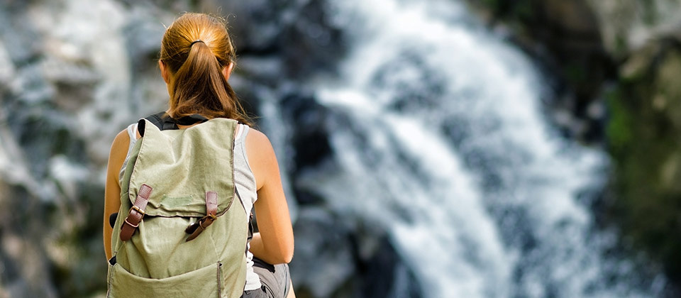 The back view of a woman relaxing in front of a waterfall in Valle Isarco