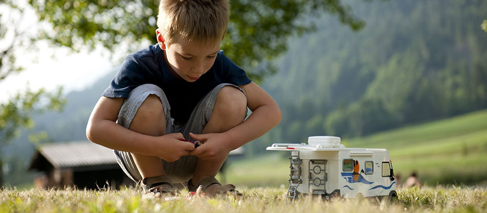 A small boy playing with a toy camper van in the mountains of South Tyrol