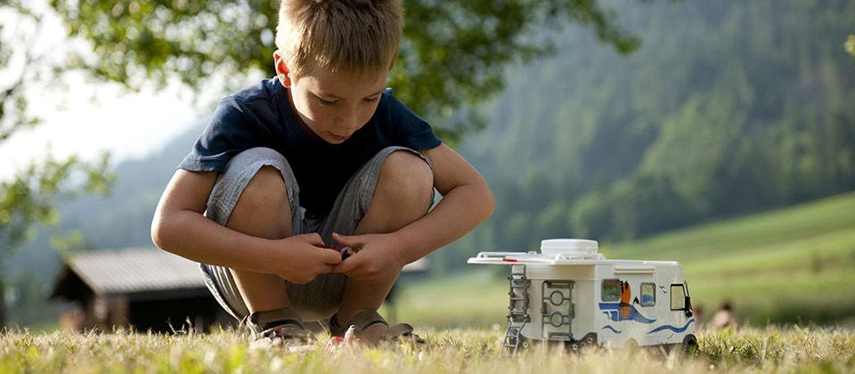 Ein kleiner Junge spielt mit einem Camper-Spielzeugauto in Südtirols Bergen