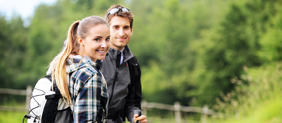 A laughing couple with backpacks in South Tyrol, wandering across the woods