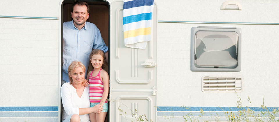 Mutter, Vater und Tochter posieren vor ihrem Wohnwagen